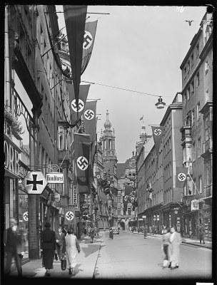 Schlossstraße, 1937: Entlang der Straße hängen unzählige Hakenkreuzfahnen, auch an der Spitze des Georgenbaus scheint eine solche zu wehen. Offenbar wussten also auch die Nazis die traditionelle Repräsentationsfunktion dieses städtebaulich weiterhin zentralen Orts für sich zu nutzen.